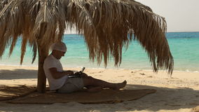 Man using laptop on the beach. Young man with laptop running under straw umbrella on the beach to type a message stock video footage