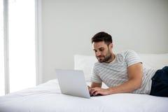 Man using laptop on bed Stock Photos