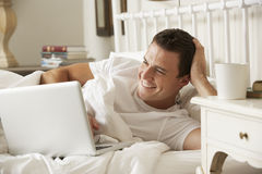 Man Using Laptop In Bed At Home Royalty Free Stock Image