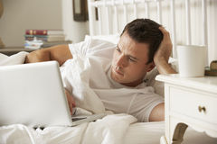 Man Using Laptop In Bed At Home Stock Photos