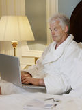 Man Using Laptop In Bed Royalty Free Stock Image