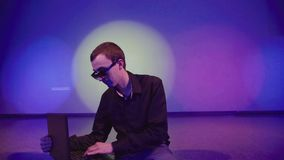 Man using a laptop being alone on the dance floor stock video footage