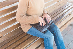 Man using laptop on bench Stock Photos