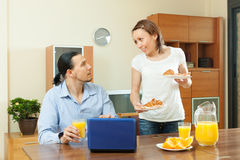 Man using  laptop during breakfast time at home Royalty Free Stock Photography