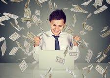 Man using laptop building online business under money rain. Young man using a laptop building online business making dollar bills cash falling down. Beginner IT royalty free stock photo
