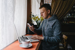 Man using a laptop and cellphone in a cafe. Young man drinking c Royalty Free Stock Images
