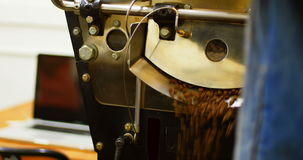 Man using laptop while coffee grinding in machine. At coffee shop stock footage
