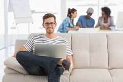 Man using laptop with colleagues in background at creative office Royalty Free Stock Image