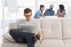 Man using laptop with colleagues in background at creative office Royalty Free Stock Photography