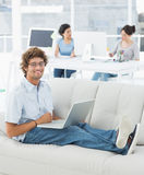 Man using laptop with colleagues at creative office Royalty Free Stock Photography
