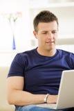 Man using laptop computer. Man sitting on sofa at home and using laptop computer Stock Photos