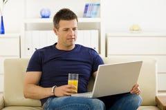 Man using laptop computer. Man sitting on sofa at home and using laptop computer Royalty Free Stock Image