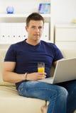 Man using laptop computer. Man sitting on sofa at home and using laptop computer Stock Photography