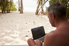 Man using a laptop computer on a beach, over shoulder view Royalty Free Stock Photos