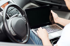 Man using laptop computer in car Stock Photo