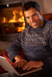 Man Using Laptop Computer By Cosy Log Fire Stock Images