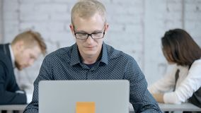Man using laptop computer and creative new business application. Focused and concentrate businessman or employee person sitting in office with modern interior stock footage