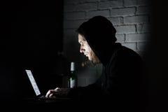 Man using laptop computer at home indoors at night. Image of young man using laptop computer at home indoors at night. Looking aside Stock Photo