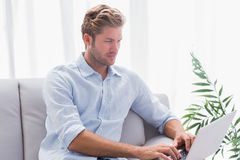 Man using a laptop on the couch in the living room Royalty Free Stock Photo