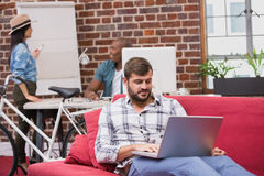 Man using laptop on couch in office Stock Image