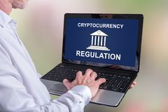 Cryptocurrency regulation concept on a laptop. Man using a laptop with cryptocurrency regulation concept on the screen stock photo