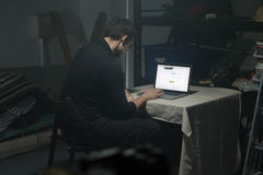 Man using laptop in dark room. Royalty Free Stock Photo