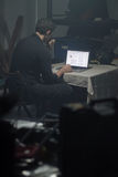 Man using laptop in dark room. Stock Photography