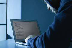 Man using laptop in room. Criminal offence. Man using laptop in dark room. Criminal offence royalty free stock image