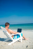 Man using laptop on deck chair at the beach Stock Photography