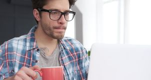 Man using laptop while drinking coffee stock video