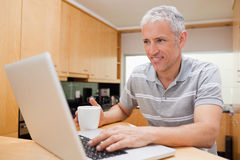 Man using a laptop while drinking tea Royalty Free Stock Photo