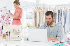 Man using laptop with fashion designer working at studio. Young men using laptop with female fashion designer working in background at the studio Royalty Free Stock Image