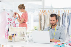 Man using laptop with fashion designer working at studio. Young men using laptop with female fashion designer working in background at the studio Stock Images