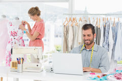 Man using laptop with fashion designer working at studio Royalty Free Stock Photography