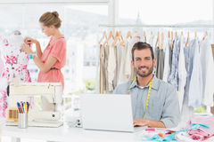 Man using laptop with fashion designer working at studio. Young men using laptop with female fashion designer working in background at the studio Royalty Free Stock Images