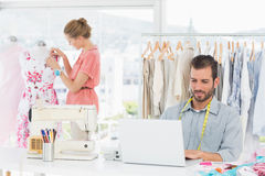 Man using laptop with fashion designer working at studio. Young men using laptop with female fashion designer working in background at the studio Stock Photo