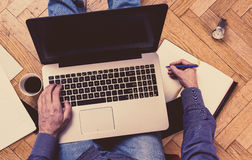 Man using laptop on a floor - working concept. Royalty Free Stock Images