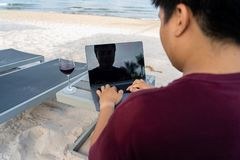 Man using laptop with glass of wine on white sand beach. Young man using laptop with glass of wine on white sand beach stock photo