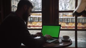 Man using Laptop with Green Screen in Cafe. Man`s hands printed text on the keyboard. Outside the winter stock video footage