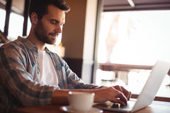 Man using laptop while having coffee Royalty Free Stock Photography