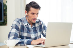 Man using laptop with headphones at home Stock Image