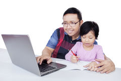Man using laptop while helps his kid studying Stock Image