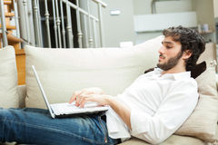 Man using a laptop in his apartment Stock Photos