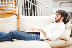 Man using a laptop in his apartment stock photo