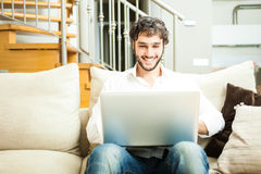 Man using a laptop in his apartment Royalty Free Stock Image