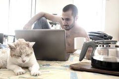 Man using laptop on his bed while drinking coffee Stock Images