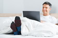 Man using a laptop in his bedroom Royalty Free Stock Photo
