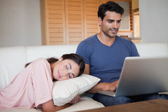 Man using a laptop while his fiance is sleeping Stock Images