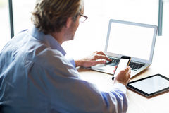 Man using laptop while holding phone in office Royalty Free Stock Photography