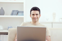 Man using laptop at home Stock Images
